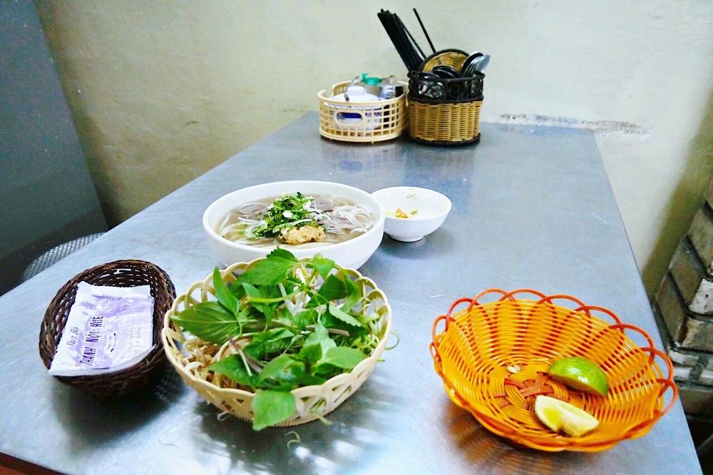 Ein typischer Tisch in Streetfood Restaurant in Saigon mit Bun Bo Hue Suppe nach einem Bun Bo Hue Rezept